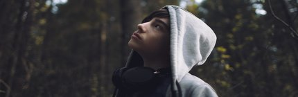 teen boy with a hoodie and headphones looks up at the trees.