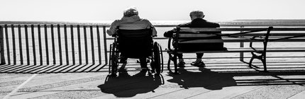 Black and white. Two elderly people sit on a bench and in a wheelchair overlooking the ocean