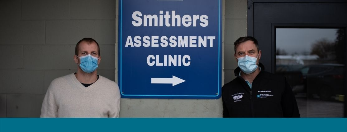 "two doctors standing in front of a sign that reads ""Smithers Assessment Clinic"""